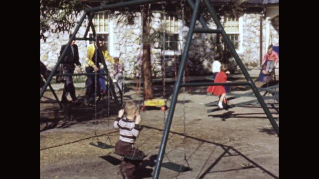 vídeos y material grabado en eventos de stock de ms children playing in playground / united states - columpiarse