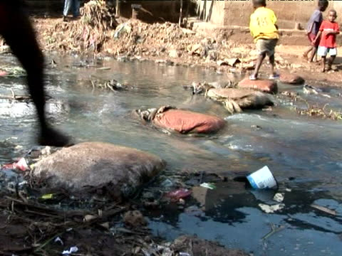Children playing in polluted river, Kroo Bay, Sierra Leone, West Africa