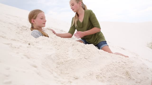 children playing in sand dunes