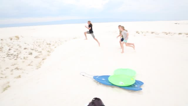vidéos et rushes de children playing in sand dunes - se déplacer vers le bas