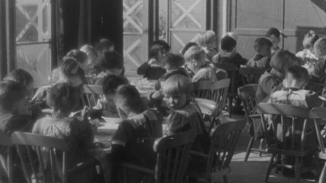 1941 montage children playing in school during immunizations of diphtheria / england - diphtherie stock-videos und b-roll-filmmaterial