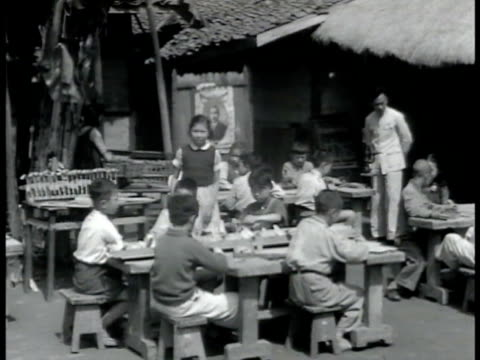 stockvideo's en b-roll-footage met children playing in school yard grade school children sitting at table outside boy in scout uniform filing airplane of wood male teacher explaining... - 1949