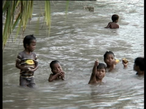 Children playing in sea close to houses, Kiribati, Central Pacific.