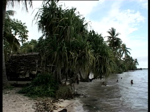 children playing in sea close to houses, kiribati, central pacific. - pacific islands stock videos & royalty-free footage