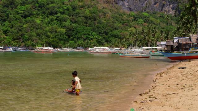 Children Playing In Sea El Nido Palawan Philippines