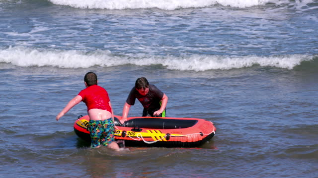 Children Playing In Sea With Inflatable Dinghy North Bay Beach Scarborough