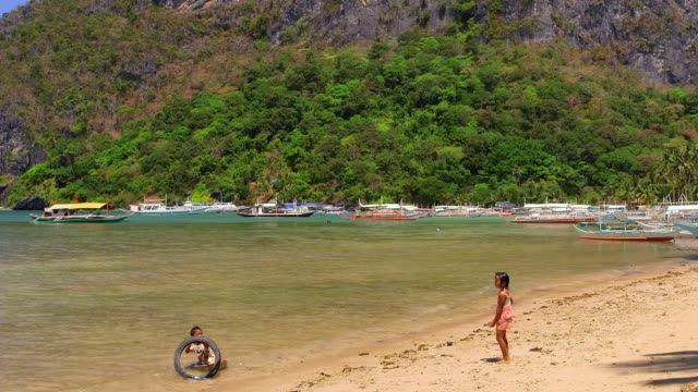 children playing in sea with metal dish tyre el nido palawan philippines no - only boys stock videos and b-roll footage