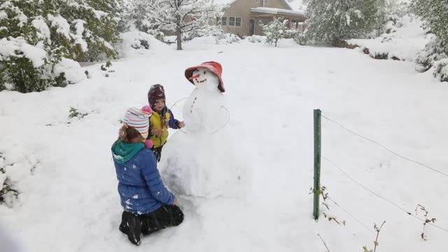 children playing in snow storm - snowman stock videos & royalty-free footage