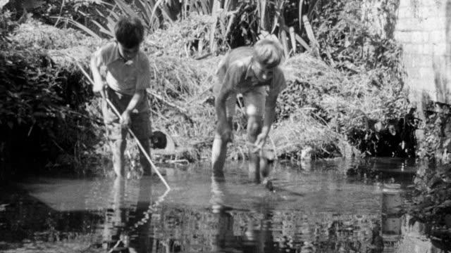1937 montage children playing in stream near arched stone bridge / essex, england - エセックス州点の映像素材/bロール