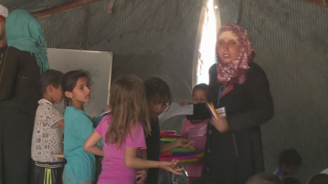 children playing in tent with woman khazir refugee camp - isil konflikt stock-videos und b-roll-filmmaterial