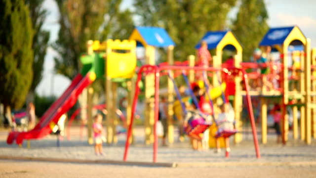 children playing in the playground - defocus - public park stock videos & royalty-free footage