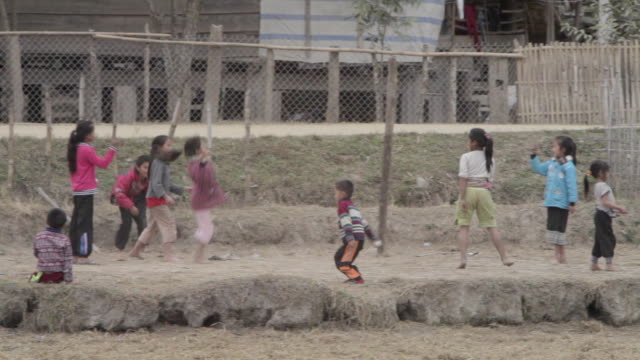 ws pan zo children playing in village / xam neua, laos - sportplatz stock-videos und b-roll-filmmaterial