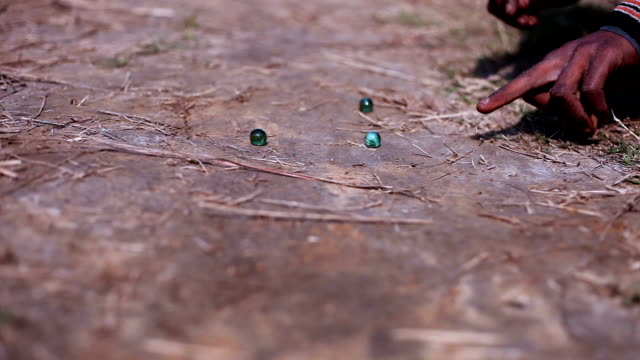 Children playing marbles in the nature