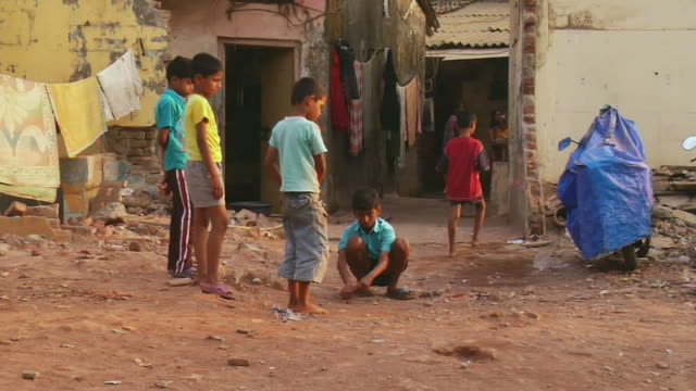 ws children playing marbles / mumbai, maharashtra, india - スラム街点の映像素材/bロール