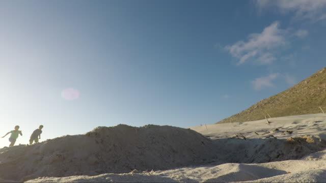 children playing on a beach at sunset - ランニングショートパンツ点の映像素材/bロール