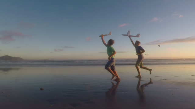 children playing on a beach at sunset - spielzeug stock-videos und b-roll-filmmaterial