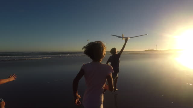 children playing on a beach at sunset - imagination stock-videos und b-roll-filmmaterial