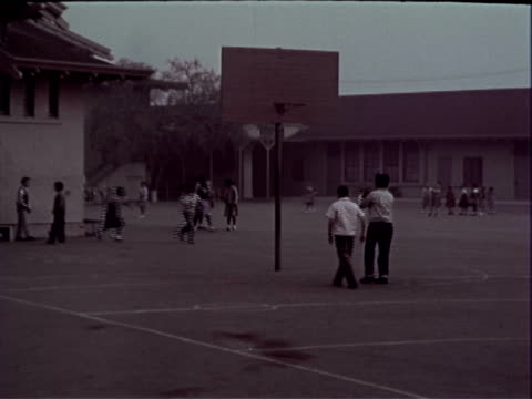 children playing on blacktop in schoolyard during recess two boys wearing blue jeans cuffed at the leg plaid shirts slicked hair running in fg / two... - plaid stock videos & royalty-free footage