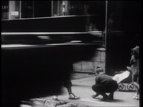vidéos et rushes de b/w 1939 children playing on city sidewalk as senior woman looks on / nyc / documentary - 1930
