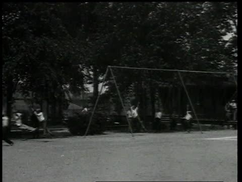vidéos et rushes de 1924 children playing on equipment at playground / detroit, michigan, united states - 1924