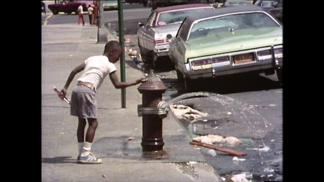 vídeos y material grabado en eventos de stock de children playing on harlem streets; new york, 1976 - boca de riego