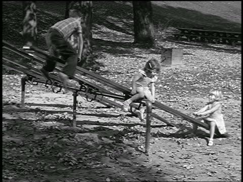 vídeos y material grabado en eventos de stock de b/w 1949 3 children playing on seesaw in park / industrial - balancín