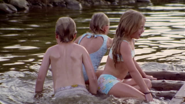 children playing on small wooden raft in pond - swimming costume stock videos and b-roll footage
