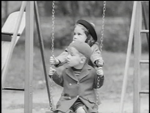 vidéos et rushes de ms children playing on swing set with father standing behind them / kansas united states - balançoire