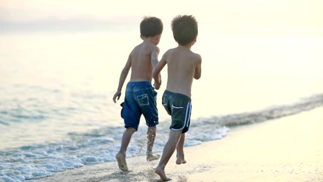 kinder spielen am strand, hd slow motion - 6 7 jahre stock-videos und b-roll-filmmaterial