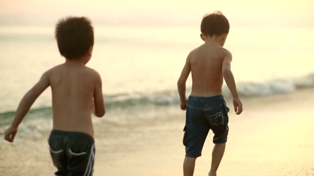 vídeos de stock e filmes b-roll de children playing on the beach,hd slow motion - crepúsculo