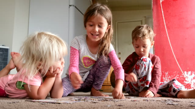 children playing on the floor solving a puzzle - puzzle stock videos & royalty-free footage
