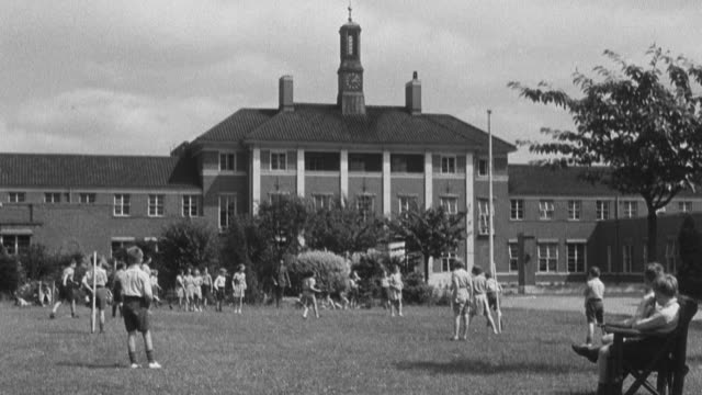 1950 montage children playing on the grounds in front of an orphanage and eating in cafeteria with staff / united kingdom - orphan stock videos & royalty-free footage
