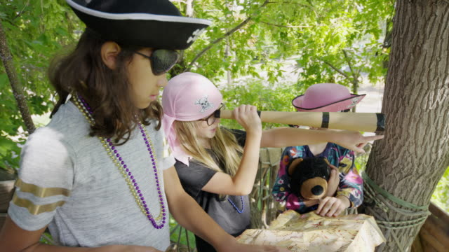 Children playing pirate in tree reading map and using telescope / Provo, Utah, United States