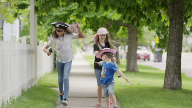 Children playing pirate running on neighborhood sidewalk / Provo, Utah, United States