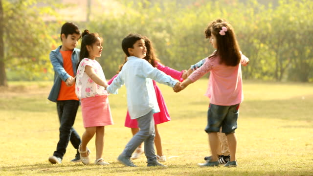 MS Children playing ring-a-ring-o'roses game in garden / Delhi, India