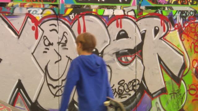 MS PAN Children playing skateboard in front of Graffiti / Paris, France