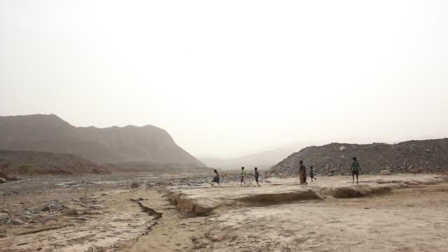 children playing soccer in the desert - エチオピア点の映像素材/bロール