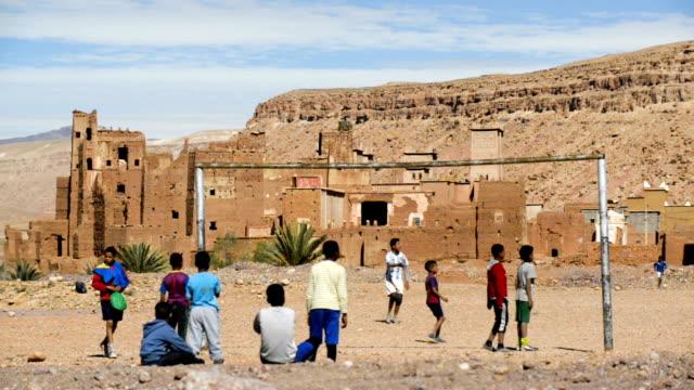 children playing soccer near moroccan kasbah, village of assfalou, near ait benhaddou, morocco, north africa - adobe bildbanksvideor och videomaterial från bakom kulisserna