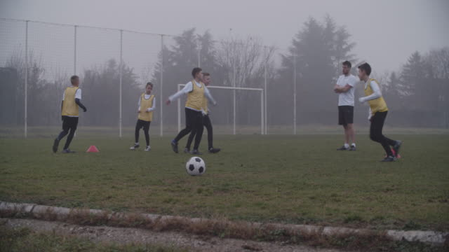 stockvideo's en b-roll-footage met 4k: kinderen te voetballen. - trainer