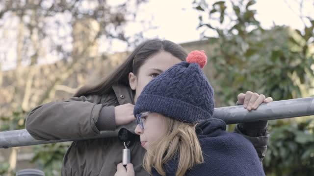 vidéos et rushes de children playing telephone game on the schoolyard during break time - aire de jeux