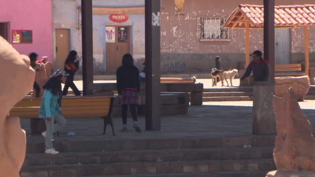 cu of children playing under metal canopy in public square on sunny day,  tiwanaku tiahuanaco/tiahuanacu, bolivia - bottle cap stock videos & royalty-free footage