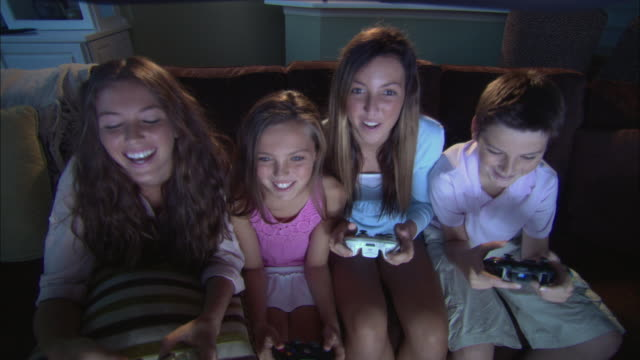 ms ha children playing video games on tv  / jacksonville, florida, usa - spielsteuerung stock-videos und b-roll-filmmaterial
