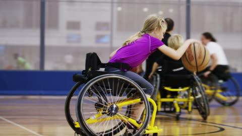 vídeos y material grabado en eventos de stock de niños jugando al básquetbol para silla de ruedas - niñas