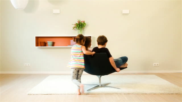 Children playing with a swivel armchair