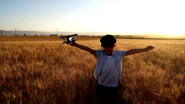 SLO MO Children playing with airplane in the field
