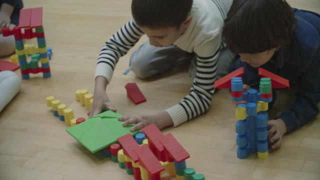 4 K: Bambini che giocano con blocchi In asilo.