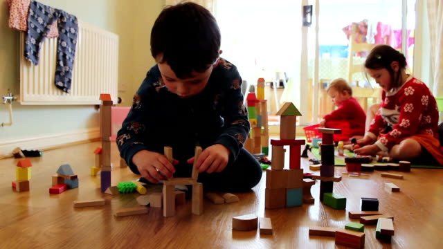 Children Playing With Building Blocks At Home