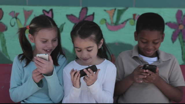 stockvideo's en b-roll-footage met ms children playing with cell phones / los angeles, california, united states - breedbeeldformaat
