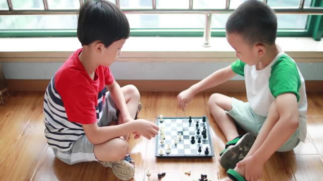 stockvideo's en b-roll-footage met kinderen spelen met schaken - alleen jongens