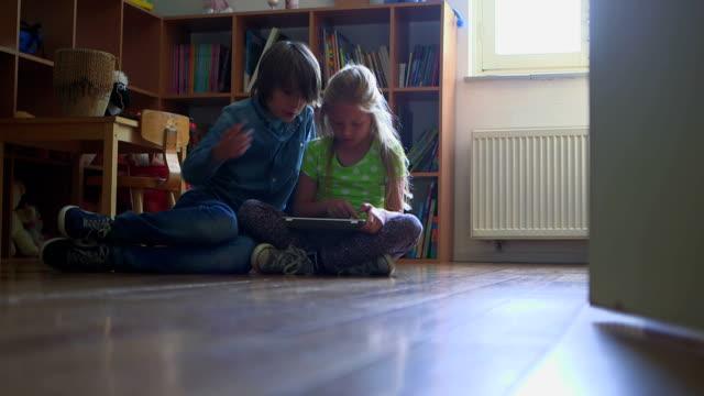 children playing with digital tablet in bedroom - auf dem boden sitzen stock-videos und b-roll-filmmaterial
